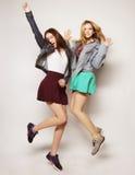 i giovani migliori amici delle ragazze dei pantaloni a vita bassa saltano Immagine Stock