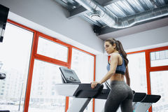 I giovani misura la donna graziosa che fa gli esercizi sulla pedana mobile Fotografia Stock Libera da Diritti
