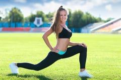 I giovani misura la donna sportiva che allunga e che riscalda Immagini Stock