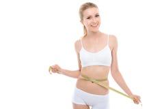 I giovani misura la ragazza bionda isolata su bianco Immagini Stock