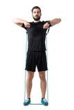 I giovani misura la spalla atletica dell'uomo che si esercita con le bande della resistenza Immagine Stock