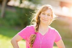 I giovani misura i vestiti di allenamento della donna adulta all'aperto che ascoltano Musi Fotografia Stock