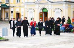 I giovani monaci camminano in trinità Sergius Lavra con gli ospiti Fotografia Stock Libera da Diritti