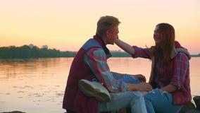 I giovani nell'amore si siedono sulle pietre contro lo sfondo del fiume, il tipo baciano la ragazza sulla fronte archivi video