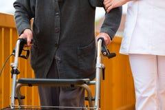 I giovani nutriscono ed anziano femminile con il blocco per grafici ambulante Fotografia Stock
