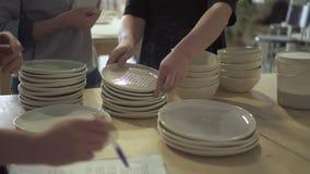 I giovani operai sta esaminando i piatti in officina ceramica archivi video