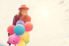 I giovani palloni della tenuta della donna dei pantaloni a vita bassa contro il cielo blu sorridono Fotografie Stock Libere da Diritti