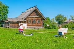 I giovani pittori nel museo di Suzdal'di architettura di legno Fotografia Stock