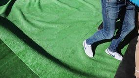 I giovani presentano il tappeto verde enorme Fase di configurazione per l'evento sulla via Operai stock footage
