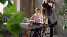 I giovani proprietari dello studio di progettazione stanno lavorando insieme nell'ufficio moderno Uno è sedentesi e scrivendo, al stock footage