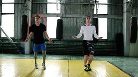 I giovani pugili caucasici stanno saltando facendo uso di una corda di salto mentre si scaldare nella studio-palestra di pugilato video d archivio