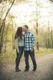 I giovani si accoppiano nel parco che si tiene per mano baciare immagini stock libere da diritti