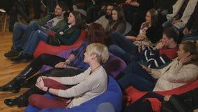 I giovani si siedono sul cuscino e guardano la manifestazione comica stock footage