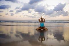 I giovani si sono adattati e donna attraente di sport nell'allenamento di pratica di yoga del tramonto della spiaggia sedendosi s Immagini Stock