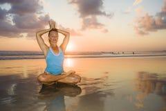 I giovani si sono adattati e donna attraente di sport nell'allenamento di pratica di yoga del tramonto della spiaggia sedendosi s Immagine Stock