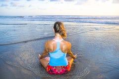 I giovani si sono adattati e donna attraente di sport nell'allenamento di pratica di yoga del tramonto della spiaggia sedendosi s Fotografia Stock