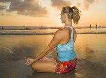 I giovani si sono adattati e donna attraente di sport nell'allenamento di pratica di yoga del tramonto della spiaggia sedendosi s Fotografia Stock Libera da Diritti