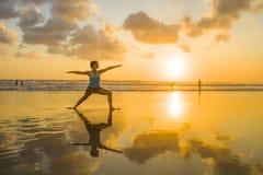 I giovani si sono adattati e donna attraente di sport nell'allenamento di pratica di yoga del tramonto della spiaggia sul sole ba Immagini Stock