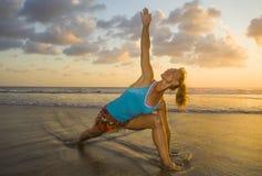 I giovani si sono adattati e donna attraente di sport nell'allenamento di pratica di yoga del tramonto della spiaggia sul sole ba Fotografie Stock