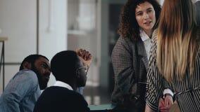 I giovani soci commerciali multietnici felici parlano all'ufficio moderno Donna caucasica attraente che parla con colleghi video d archivio