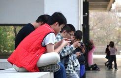 I giovani sono occupati con i loro Smartphones Fotografia Stock