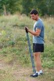 I giovani sport muscolari bei equipaggiano l'esercitazione dell'esterno all'aperto con l'elastico Fotografia Stock Libera da Diritti