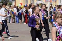 I giovani sportivi della città mette in mostra le scuole Celebrazione primo maggio, il giorno della molla e del lavoro Parata di  Immagini Stock