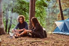 I giovani studenti felici stanno scaldando vicino al falò nella foresta verde fotografia stock