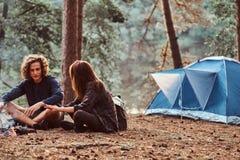 I giovani studenti felici stanno scaldando vicino al falò nella foresta verde immagini stock libere da diritti