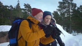 I giovani sull'inverno fanno un'escursione in montagne, viaggiatori con zaino e sacco a pelo camminanti sulla neve video d archivio