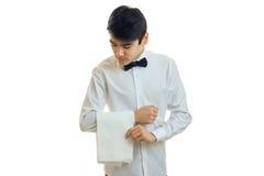 I giovani supporti attraenti del cameriere in una testa di piegamento della camicia bianca e tiene a disposizione un asciugamano Fotografia Stock