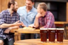 I giovani tipi allegri stanno comunicando in pub Fotografia Stock Libera da Diritti