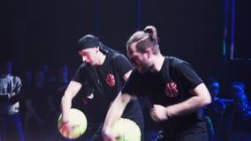 I giovani tipi attivi barbuti attraenti in vestiti neri eseguono con la palla gialla archivi video