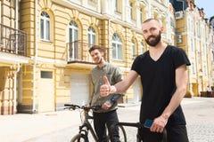 I giovani tipi bei dei pantaloni a vita bassa stanno guidando le biciclette Fotografia Stock Libera da Diritti