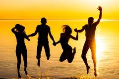 I giovani, i tipi e le ragazze, studenti stanno saltando contro i precedenti del tramonto Fotografia Stock