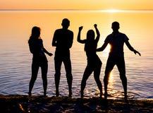I giovani, tipi e ragazze, stanno ballando sulla spiaggia al tramonto Immagine Stock