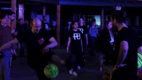 I giovani uomini attivi bei in vestiti allegri neri eseguono con la palla gialla stock footage
