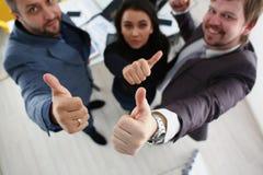 I giovani uomini d'affari allegri hanno dita di manifestazione di risultati di successo grandi Immagini Stock Libere da Diritti