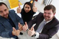 I giovani uomini d'affari allegri hanno dita di manifestazione di risultati di successo grandi Fotografia Stock