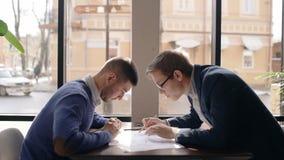 I giovani uomini d'affari stanno discutendo il progetto startup, sedentesi alla tavola in caffetteria archivi video