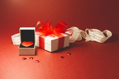 I give you my heart. A red velvet heart in a white jewelry box, a white gift box with red ribbon and small shiny red decorative hearts on red background Stock Photography
