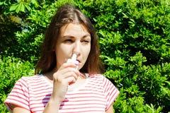 I gocciolamenti della ragazza hanno bloccato il naso dall'allergia Donna con spruzzo respiratorio per il naso nella fioritura di  immagini stock libere da diritti