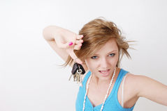 I Got Keys. Female fashion model standing against a white back ground holding up a set of keys. with with facial expressions and wind swept hair Royalty Free Stock Photography