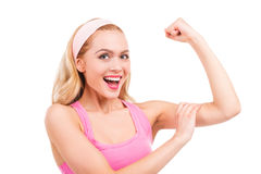 I got perfect biceps!. Beautiful pin-up blond hair woman in pink shirt touching her bicep and smiling while standing isolated on white background Royalty Free Stock Photography