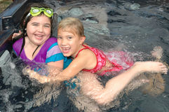 I got you!. To kids chase each other around the pool or hot tub. Summer fun. Best friends Stock Photos