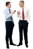 I got your message my friend. Smiling male executives sharing their contacts royalty free stock image