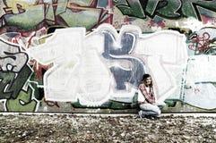 I graffiti murano e ragazza fotografia stock