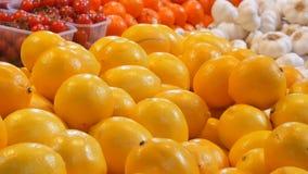 I grandi bei limoni gialli maturi sono sulla fine del contatore del mercato sulla vista video d archivio