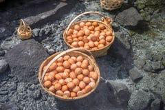 I grandi canestri delle uova bollite sotto acqua calda accumulano Fotografia Stock Libera da Diritti