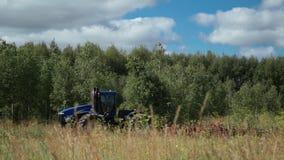 I grandi erpici blu del trattore sistemano vicino ad una foresta della betulla video d archivio